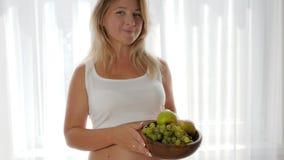 Kobieta z dużym nagim brzuszkiem je winogrona i utrzymuje owocowego pobliskiego okno, zdrowy odżywianie zbiory