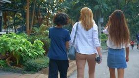 Kobieta z dzieci, syna i córki nastolatkami z kamerą, chodzi przez ulic wielki nowożytny miasto zbiory
