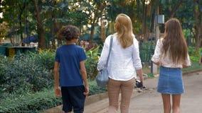 Kobieta z dzieci, syna i córki nastolatkami z kamerą, chodzi przez ulic wielki nowożytny miasto zdjęcie wideo
