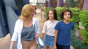Kobieta z dzieci, syna i córki nastolatkami z kamerą, chodzi przez ulic wielki nowożytny miasto zbiory wideo