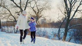Kobieta z dzieckiem śmia się w zima parku Dziewczyna biega o mamie i cieszy się dobrego zima dzień zbiory wideo