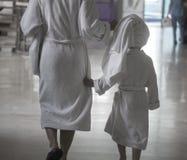 Kobieta z dzieckiem chodzi w zdroju centrum w białych bathrobes zdjęcie royalty free