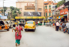 Kobieta z dzieckiem krzyżuje starą indyjską ulicę z kinowym teatrem i hotelami Zdjęcia Royalty Free