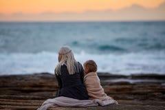 Kobieta z dziewczyną cuddling na seashore obraz royalty free
