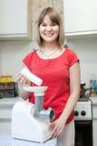 Kobieta z elektrycznym mięsnym siekaczem obraz stock