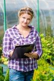 Kobieta z falcówką czytania nagrywał przyrosta rośliny fotografia stock