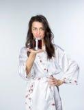 Kobieta z filiżanką herbata w peignoir wczesnym poranku Zdjęcie Stock