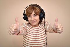 Kobieta z hełmofonami pokazuje aprobaty obrazy stock