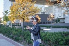 Kobieta z hełmofonami sprawdza jej wiszącą ozdobę przed biurowym terenem obraz stock