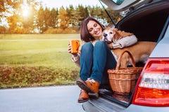 Kobieta z jej psem herbacianego czas podczas ich jesień samochodu trav zdjęcie royalty free