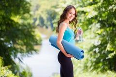 Kobieta z joga matą outdoors Obrazy Royalty Free