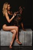 Kobieta z kędzierzawym blondynem w czarnym kostiumu kąpielowego obsiadaniu z Doberman Dziewczyna trzyma Doberman łańcuch długi Fotografia Royalty Free
