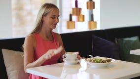 Kobieta z kawowym dzwoni smartphone przy restauracją zbiory