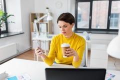 Kobieta z kawowym używa smartphone przy biurem zdjęcie royalty free