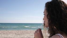Kobieta z koktajlem na tropikalnej plaży w ręce, dziewczyna W okularach przeciwsłonecznych pije sok przy nadmorski, ładna kobieta zbiory