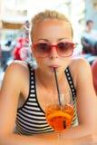 Kobieta z koktajlem w ulicznej kawiarni Zdjęcia Stock