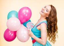 Kobieta z kolorowymi balonami i lizakiem Zdjęcia Stock