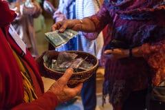 Kobieta z kolorowymi ubraniami stawia 10 dolarów kanadyjskich w kosz zdjęcia royalty free