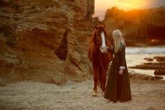 Kobieta z koniem na skalistym seashore zdjęcia royalty free