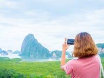 Kobieta z krótkim włosy używa mądrze telefon bierze fotografii seascape widok obraz royalty free