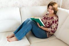 Kobieta z książkowym obsiadaniem na kanapie w pokoju Zdjęcie Stock
