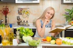 Kobieta z kucharstwo książki obsiadaniem przy kuchennym stołem Obrazy Stock