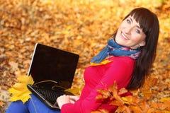 Kobieta z laptopem w jesień parku Obraz Stock