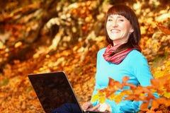 Kobieta z laptopem w jesień parku Zdjęcia Royalty Free