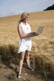 Kobieta z laptopem w polu jęczmień Zdjęcia Royalty Free
