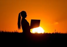 Kobieta z laptopem w pszenicznym polu przy półmrokiem Obrazy Royalty Free