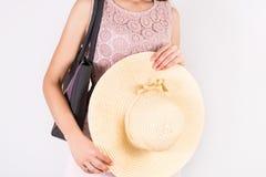 Kobieta z lato słomianym kapeluszem w ręce i torebka na ramieniu z koronkową śmietanką ubieramy fotografia royalty free