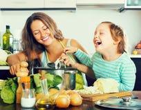Kobieta z małą dziewczynką gotuje w domu obrazy stock