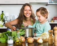 Kobieta z małą dziewczynką gotuje w domu zdjęcie royalty free