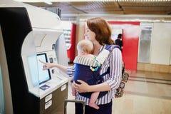 Kobieta z małym dzieckiem w dziecko przewoźniku robi jaźni - sprawdza wewnątrz przy powietrzem obrazy stock