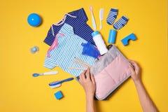 Kobieta z macierzyńskimi torby i dziecka akcesoriami na koloru tle obrazy royalty free