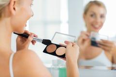 Kobieta z makeup muśnięciem i podstawa przy łazienką Obraz Royalty Free