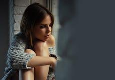 Kobieta z makeup na ładnym twarzy spojrzeniu przez cały okno Kobieta siedzi z nogami na nadokiennym parapecie ładna kobieta, kopi Fotografia Stock