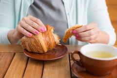 Kobieta z menchia manicure'em drzeje małego kawałek od wielkiego croissant Zdjęcia Stock