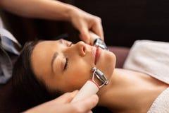 Kobieta z microcurrent twarzy massager w zdroju Zdjęcie Royalty Free