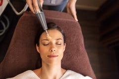 Kobieta z microcurrent twarzy massager w zdroju Fotografia Stock