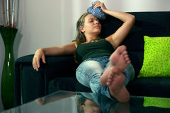 Kobieta z migreny obsiadaniem na kanapie z lodową torbą na głowie obrazy stock