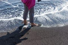 Kobieta z nagimi ciekami w wodzie na czarnej plaży Fotografia Stock
