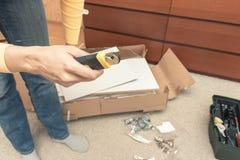 Kobieta z nożowym odpakowaniem boksuje z nowym meble i przygotowywa gromadzić, mebli szczegóły na podłodze za ona obrazy royalty free
