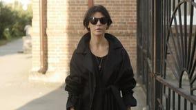 Kobieta z okulary przeciwsłoneczni pobliską bramą zdjęcie wideo