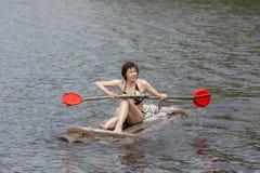 Kobieta z paddle na drewnianej tratwie zdjęcie royalty free