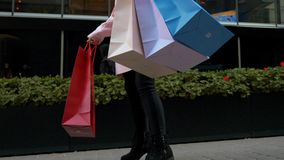 Kobieta z papierowymi torbami w rękach tańcząca na ulicy na tle zielonego kwiatka fasady Mall zbiory