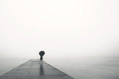 Kobieta z parasolem kontempluje pokojowo przed morzem fotografia royalty free