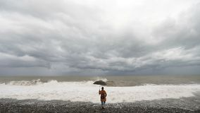 Kobieta z parasolowym pobliskim burzowym morzem zbiory