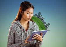 Kobieta z pastylką przeciw kuli ziemskiej, budynkom i błękitnej zieleni tłu obrazy stock
