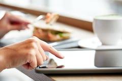 Kobieta z pastylka komputerem osobistym i panini ściskamy przy kawiarnią Zdjęcia Stock